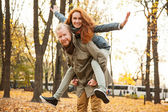 Love story. Autumn Park. Man and woman in a city park tells the story of his love. Happy people having fun. Woman on top of a man on his back. — Stok fotoğraf