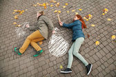 Love story. Autumn Park. Man and woman in a city park tells the story of his love. Painted on earth concept litters loving couple. Man escapes with a painted bag from his woman. — Stockfoto