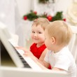Boy and girl playing on white piano — Stock Photo #41052097
