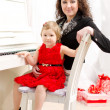 Mother and daughter playing on white piano — Stock Photo
