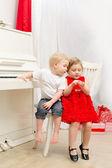 Boy with girl sitting near white piano — Stock Photo