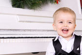 Happy boy near white piano — Stock Photo