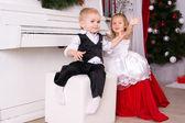 Boy and girl sitting near white piano — Stok fotoğraf