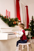 Boy playing the piano on eve of Christmas — Foto Stock