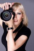 Elegant sexy girl holding a camera — Stock Photo