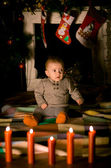 Baby sitting on  floor near fireplace — Stock Photo