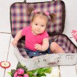 Baby girl sitting in old vintage suitcases — Stock Photo