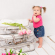 Baby girl standing near old vintage suitcases — Stock Photo