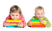 Little boy and girl with piles of books — Stock Photo