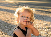 Curly girl in rays of setting sun in park — Stock Photo