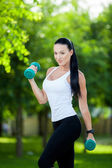 Portrait of cheerful woman in fitness wear exercising with — Stock Photo