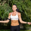A sportive beautiful woman in a park with a rope — Stock Photo #50173579