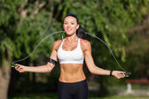 A sportive beautiful woman in a park with a rope — Stock Photo