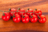 Cherry tomatoes on wooden table — Stock Photo
