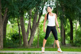 Young attractive sport girl in white and black sport wear in the park, fitness, sport — Stock Photo