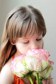 Girl smells the flowers — Stock Photo