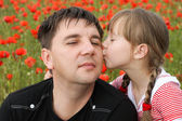 Girl kissing on the cheek father — Stock Photo