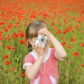 Girl photographs field with poppies — Stock Photo