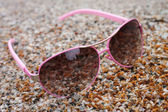 Rose colored glasses on the beach — Stock Photo