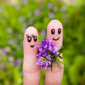 Happy couple. Man is giving flowers to a woman. — 图库照片