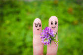 Happy couple. Man is giving flowers to a woman. — Stock Photo