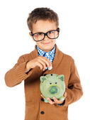 Smile young boy with glasses puts money into a piggy bank — Stock Photo