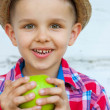 Happy boy in a colorful shirt while eating green apple — Stock Photo #42810753