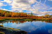Lake in autumn forest under swimming by clouds — Stock Photo