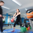 Action shot of woman exercising with kettle bell — Stock Photo
