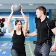 Using medicine ball with personal trainer — Stock Photo #41825117