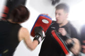 Action shot punching the pads — Stock Photo