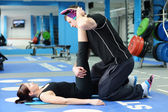 Leg stretching with personal trainer — Stock Photo
