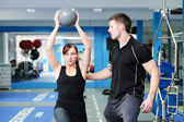 Using medicine ball with personal trainer — Stock Photo
