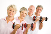 Mature older people lifting weights — Stock Photo