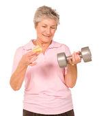 Mature older lady choosing diet or exercise — Stok fotoğraf