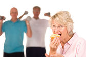 Mature lady eating cake at the gym — Stock Photo