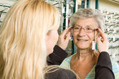 Att välja glasögon hos optikern — Stockfoto