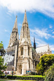 Vienna, Austria - famous Votivkirche (Votive Church) with trees and blue sky — Stock Photo