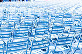 Rows of empty metal chair seats in blue light — Stock Photo