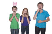 Three young children eating easter eggs — Stock Photo