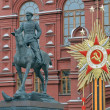 Постер, плакат: Russia Moscow Monument to Marshal Zhukovon the background of the Historical Museum in Moscow