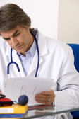 DOCTOR WITH MEDICAL RECORD — Stock Photo