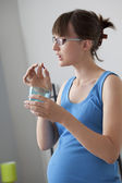 PREGNANT WOMAN TAKING MEDICATION — ストック写真