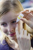 WOMAN USING EYE LOTION — Stock fotografie