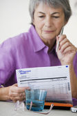 ELDERLY P. FILLING OUT FORMS — Stock Photo