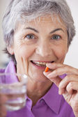 ELDERLY PERSON TAKING MEDICATION — Stock Photo