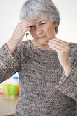 ELDERLY PERSON WITH HEADACHE — Stockfoto