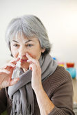 ELDERLY PERSON USING NOSE SPRAY — Stock Photo