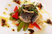 Sea bass fillet with spring vegetables — Stock Photo