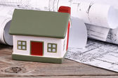 Projects of houses with model of a house — Stock Photo